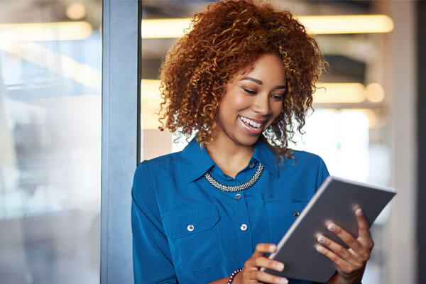 Smiling woman uses tablet device