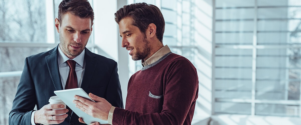 Two businessmen looking at computer tablet device